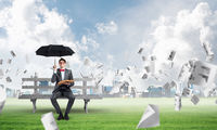 young businessman with an umbrella and a book