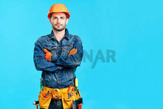 Portrait of confident handsome male construction worker with crossed arms and copy space