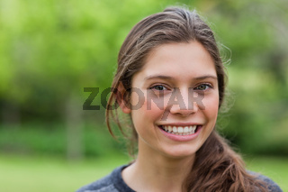Smiling young woman looking at the camera while standing in a park