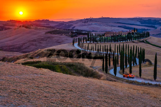 Tuscany, Crete Senesi rural sunset landscape. Countryside farm, cypresses trees, green field, sun light and cloud. Italy, Europe,Summer rural landscape with curved road in Tuscany, Italy, Europe