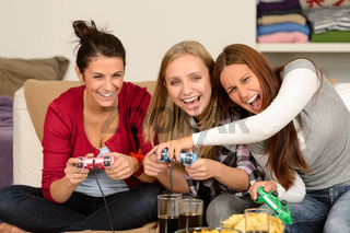 Laughing young girls playing with video games