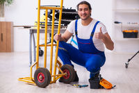 Young male repairman repairing trolley indoors