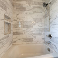 Square frame Modern bathroom interior with alcove bathtub with marble tiles surround