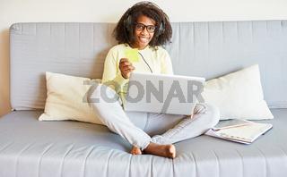Afrikanische Frau mit Laptop Computer auf Sofa