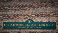 The Old Bushmills Distillery Co. Ltd Licensed to distil in 1608 sign on rustic brick wall