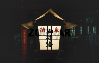 Japanese lantern in front of torii gate at Nonomiya Shrine in the evening in Kyoto, Japan