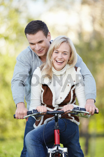 Young attractive couple rides a bicycle in the park