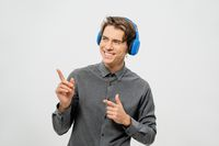 Happy smiling young guy in grey shirt standing listening music wearing blue wireless headphones pointing fingers sideways. Funny young guy listen to his favourite track or song