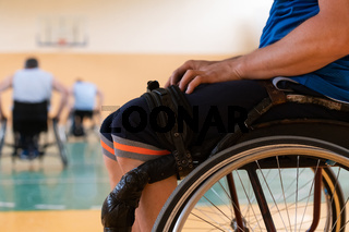 Close up photo of wheelchairs and handicapped war veterans playing basketball on the court