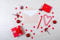 Composition of christmas decorations with envelope, baubles, candy canes, stars on wooden background