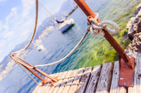 Sailing: Wooden dock pier, sailing boats in the background.