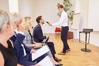 Referent mit Mikrofon stellt Fragen an Seminar Teilnehmer