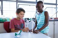 Caucasian boy and african american boy holding windmill models in science class at elementary school