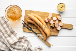 Sliced smoked frankfurter sausages on cutting board.