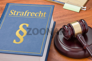 A law book with a gavel -  German Translation of Criminal law - Strafrecht