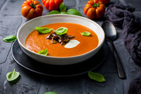 Homemade tomato soup with roasted eggplant and basil on dark background