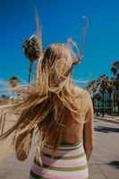 Back view of long-haired girl walking on the beach in sunny day. Vertical.