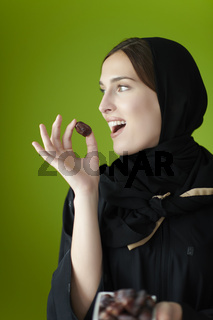 Young muslim girl wearing traditional muslim clothes holding dried dates
