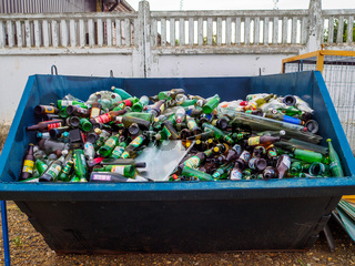A large garbage bin filled with used glass bottles.