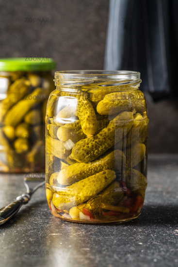 Small pickles. Marinated pickled cucumbers in jar.
