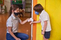 Kindergärtnerin mit Mundschutz beim Fieber messen