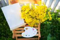 A palette of watercolor multicolored paints stands on a wooden chair and a bouquet of yellow flowers, creative hobby, drawing on the street.