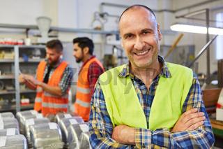 Glücklicher Facharbeiter vor Lager einer Metallfabrik