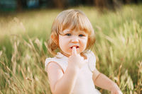 little girl sits outdoors and holds a finger in his mouth