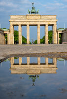The famous Brandenburger Tor in Berlin with no people reflected in a puddle