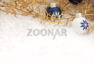 Goldene Weihnachtsdeko mit Schnee und Weihnachtskugeln
