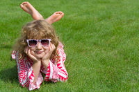 Child lies relaxed on a green meadow
