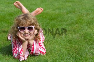 Kind liegt entspannt auf grüner Wiese