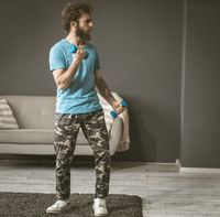 A young man sports in his room. Exercise with dumbbells. The curly-haired guy is holding dumbbells in his hands.