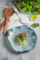 Modern ceramic bowl with wooden salad cutlery and bowl of lettuce on stone background