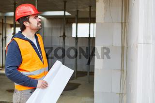 Baugutachter mit Bauzeichnung kontrolliert Baumängel