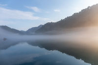 river covered with white fog in sunrise