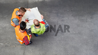 Bauarbeiter mit Bauplan bei Hausbau von oben