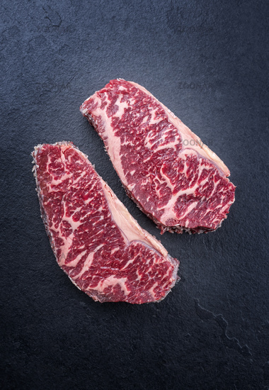 Raw dry aged wagyu roast beef steak offered as top view on a black board with copy space