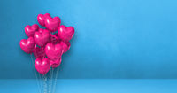 Pink heart shape balloons bunch on a blue wall background. Horizontal banner.