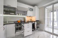 Luxurious white modern kitchen interior, drawers pulled out, dishwasher's door open