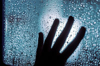Depression and goodbye concept: dark silhouette of human hand on window with rain drops