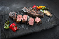 Barbecue dry aged wagyu roast beef steak with paprika and zucchini offered as close-up on a charred wooden board