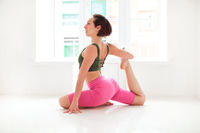 Young slender fit woman in sportwear performing yoga pose, isolated over white studio background