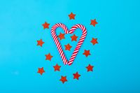 Composition of candy canes with red stars on blue background