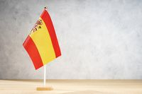 Spain flag on white textured wall. Copy space for text, designs or drawings