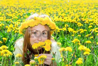 Young pretty woman in wreath of dandelions in the meadow solar day