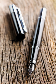 the fountain pen on old wooden background