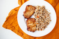 Delicious and appetizing pork tenderloin steak, grilled with buckwheat and vegetables, is on the table along with an orange napkin.
