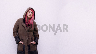 young woman with hooded parka pink hair piercings and tattoos against wall with copy space
