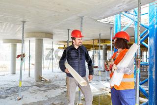 Architekt mit Bauplan und Arbeiter planen Bauarbeiten